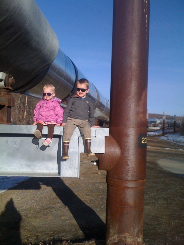 Amelia and Levi sit on the Alaska Pipeline