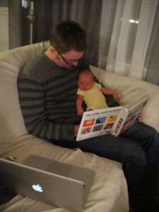 Daddy reading a book...but I think Axel is already enticed by the Apple...