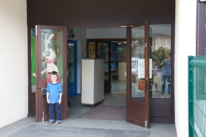 Levi in front of his school on our first visit there.  Amelia's classroom is the blue door just inside.