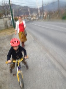 A blurry photo of a family trip to the grocery store - Levi's first on his bike.